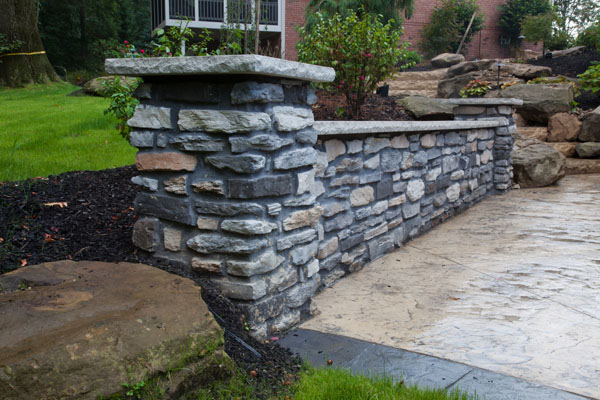 Decorative Stone Wall Along Concrete Patio Decorative Stone Wall Along  Concrete Patio